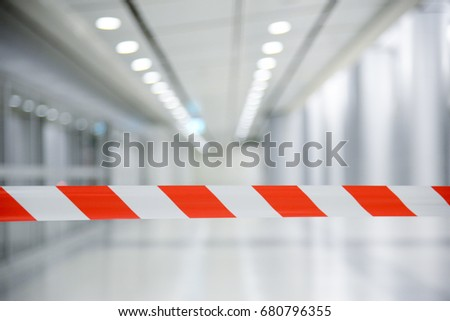 Red and White Lines of barrier tape. At subway station of airport background.Red White warning tape pole fencing is protects for No entry Royalty-Free Stock Photo #680796355