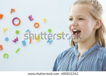 Copy space with little girl opening mouth in speech therapy office Royalty-Free Stock Photo #680832262