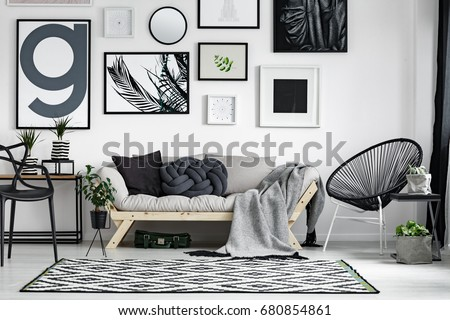 Wooden sofa with dark pillows in scandi style living room Royalty-Free Stock Photo #680854861