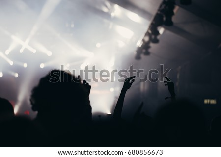 Stage lights and crowd of audience with hands raised at a summer music festival. #680856673