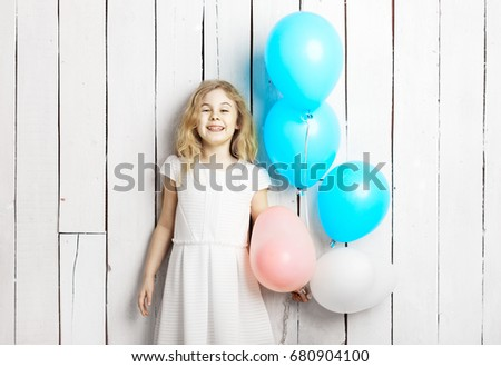 Cheerful little blonde girl with balloons on white wood backgrou
