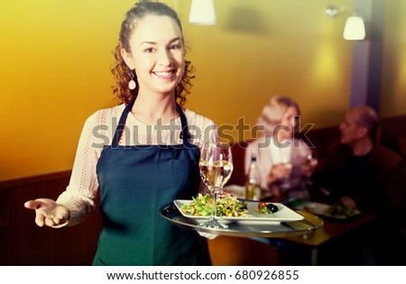 Positive young waitress greeting customers at table in restaurant #680926855