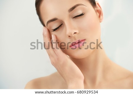 Closeup view of beautiful young woman with natural lips makeup touching face on light background #680929534