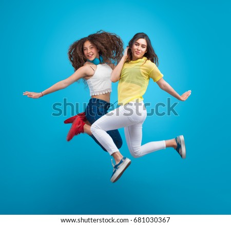 Two young stylish girls jumping for photo in studio on blue background. #681030367