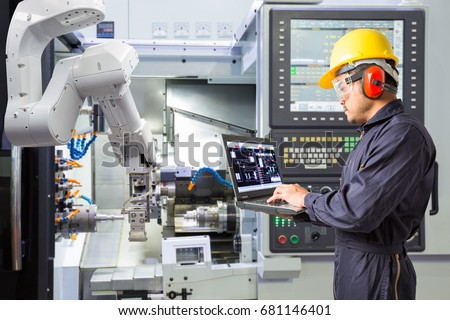 Maintenance engineer using laptop computer control automatic robotic hand with CNC machine in smart factory. Industry 4.0 concept #681146401