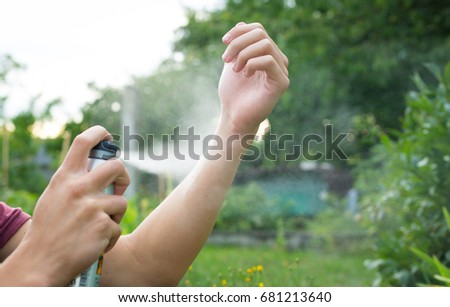 Young man spraying mosquito / insect repellent in the forrest, insect protection #681213640
