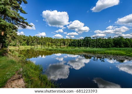 reflection of clouds in the lake with forest  and trees in background #681223393