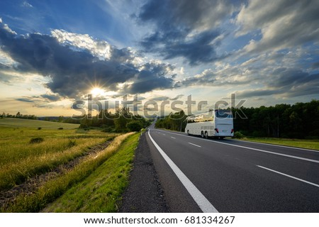 Bus traveling on the asphalt road in a rural landscape at sunset with dramatic clouds #681334267