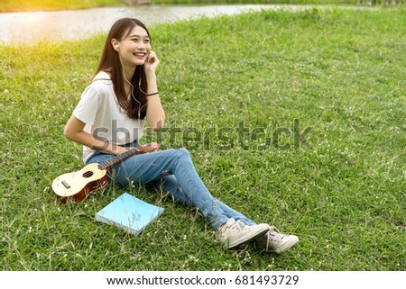 Young asian girl artist with ukulele classic, book and listening music singer pop solo sound smiling lifestyle in park nature summer of vacation time. #681493729