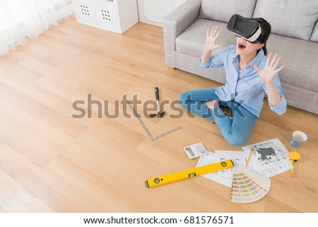 elegant pretty woman wearing VR technology glogges sitting on floor and viewing new house design drawing video feeling surprised. high angle view photo. #681576571