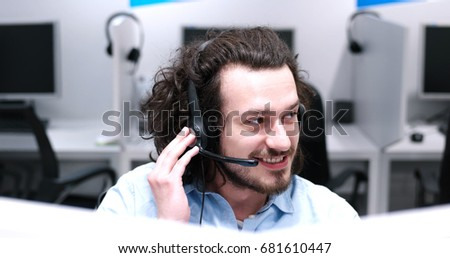 young smiling male call centre operator doing his job with a headset #681610447
