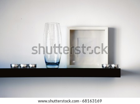 black shelf with vase,frame and candles