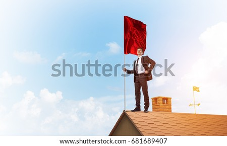 Businessman standing on house roof and holding red flag. Mixed media #681689407