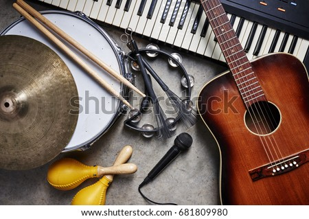 a group of musical instruments including a guitar, drum, keyboard, tambourine. Royalty-Free Stock Photo #681809980