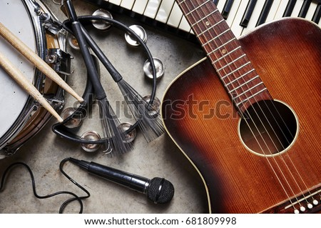 a group of musical instruments including a guitar, drum, keyboard, tambourine. Royalty-Free Stock Photo #681809998