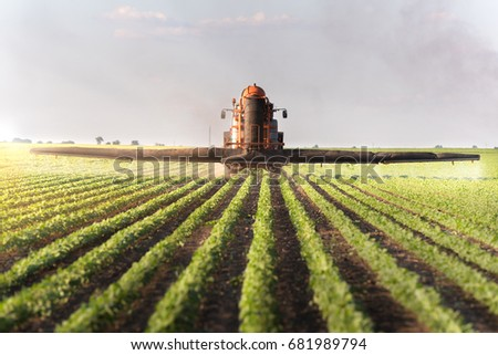 Tractor spraying soybean field at spring  #681989794