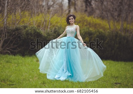 A beautiful graduate girl is spinning in a clearing in a blue fluffy dress. Elegant young woman in a beautiful dress in the park. Art photo. #682105456