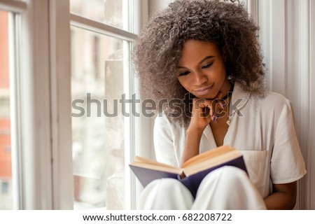 Pretty afro-american girl with reading a book sitting on the windowsill. Royalty-Free Stock Photo #682208722