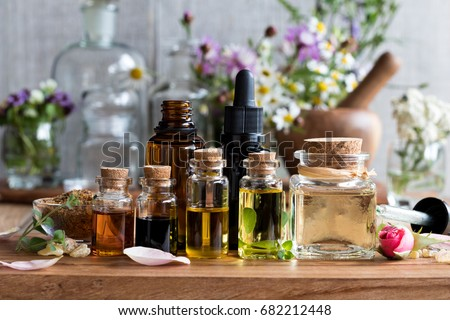 Selection of essential oils, with herbs and flowers in the background Royalty-Free Stock Photo #682212448