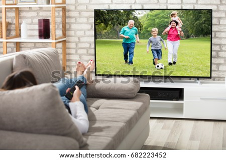 Woman Lying On Couch Watching Television At Home Royalty-Free Stock Photo #682223452