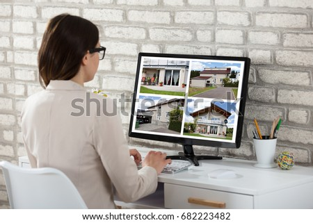 Rear View Of A Businesswoman Looking At House Photos On Computer In Office