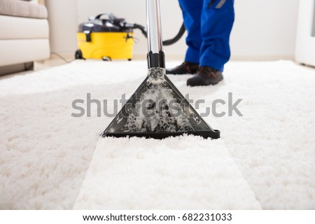 Close-up Of A Janitor Cleaning Carpet With Vacuum Cleaner At Home Royalty-Free Stock Photo #682231033