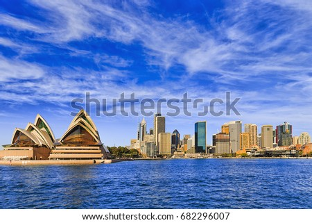 Panorama of Sydney city CBD behind Circular quay across Harbour with tall towers of business and office high-rises on a sunny bright day. Royalty-Free Stock Photo #682296007