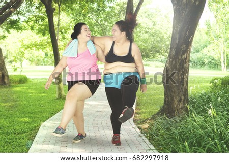 Picture of two overweight women laughing together while exercising in the park