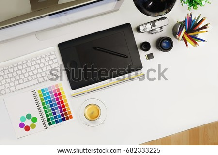 Creative professional designer's desk from above. Designer workspace top view with essential elements on white table.