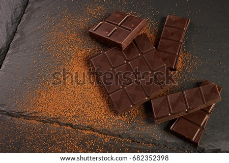 Close-up of broken chocolate pieces and cocoa powder on dark stone background with copy space. #682352398