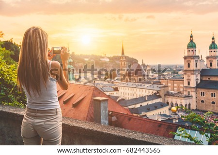 Tourist taking a photo with mobile of beautiful sunset in Salzburg Austria