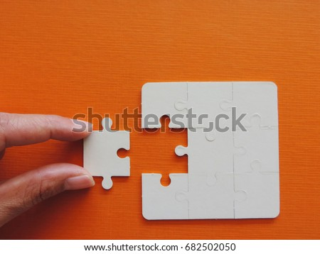 Concept of business,hand holding a puzzle piece on puzzle background. #682502050