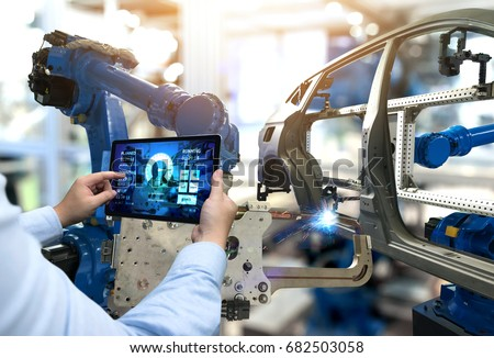 Engineer hand using tablet with machine real time monitoring system software. Automation robot arm machine in smart factory automotive industrial Industry 4th iot , digital manufacturing operation. Royalty-Free Stock Photo #682503058