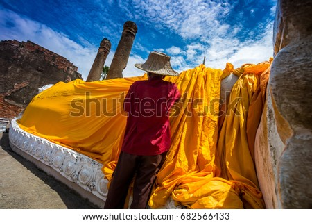 The old man was guarding the yellow cloth on the statue at a Thai temple in Ayutthaya. #682566433
