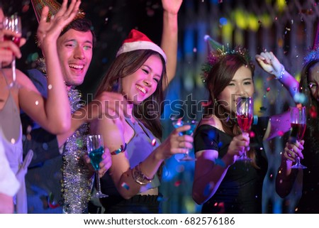 Motion blur movement of Cheerful Young people dancing and showered with confetti on a club party on Friday night hangout. Nightlife and people concept.In selective Focus on happy people face. #682576186