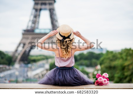 Blond girl with curls holding her hat and looking at the Eiffel tower in Paris from the roof top of the Trocadero place