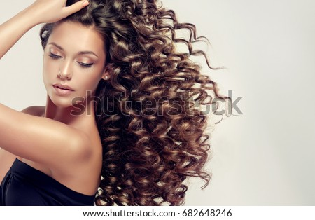 Brunette  girl with long  and   shiny curly  hair .  Beautiful  model woman  with wavy hairstyle  Royalty-Free Stock Photo #682648246