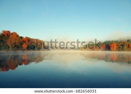 Lake fog with Autumn foliage and mountains with reflection in New England Stowe #682656031