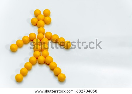 Yellow balls of vitamins in the form of a toy man on a white background #682704058