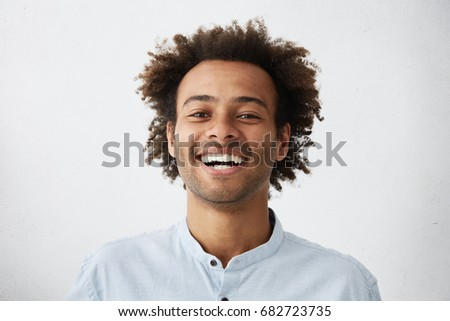 People, lifestyle, happiness and positive human expressions. Studio shot of attractive young dark-skinned student with Afro hairstyle laughing at good joke, looking at camera with carefree smile #682723735