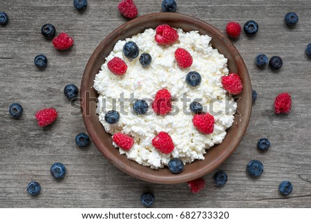 cottage cheese with fresh raspberries and blueberries in a bowl for healthy breakfast with ripe berries over rustic wooden background. top view #682733320