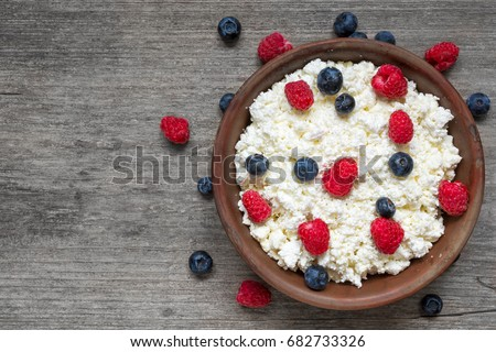 cottage cheese with fresh raspberries and blueberries in a bowl for healthy breakfast with ripe berries over rustic wooden background. top view #682733326