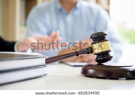 Judge gavel with Justice  lawyers having team meeting at law firm in background. Concepts of law. #682834900