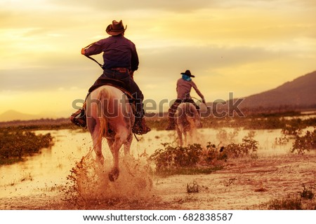 Cowboy on horseback on water and mountain background