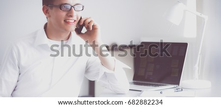 Young businessman working in office, sitting at desk #682882234