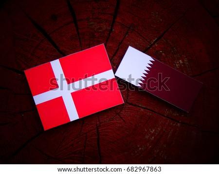 Danish flag with Qatari flag on a tree stump isolated #682967863