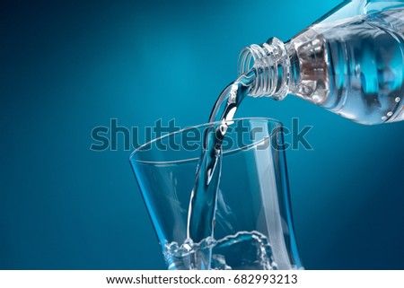 Pouring fresh mineral water from a bottle into a glass, hydration and diet concept #682993213