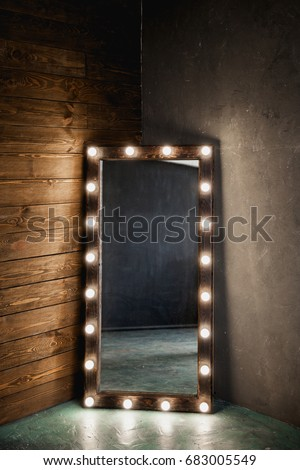 Long dressing mirror with light bulbs stands on the floor against a wooden and concrete wall #683005549