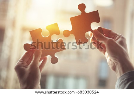 Closeup hand of woman connecting jigsaw puzzle with sunlight effect, Business solutions, success and strategy concept Royalty-Free Stock Photo #683030524