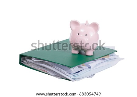 Piggy bank on top of a thick office binder with haphazardly filed paperwork isolated on white with copy space #683054749